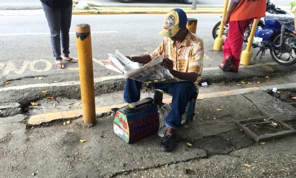 Puerto Plata-Le cireur de bottes et son journal-Crédit : Osman
